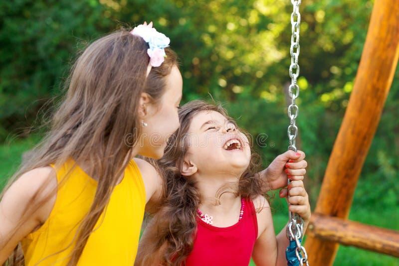 Twee gelukkige, mooie meisjes die aan de zwaai zitten en lachen op warme zomerdag stock afbeeldingen