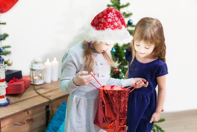 Twee gelukkige mooie meisjes kijken in de zak die van de Kerstmisvakantie van binnenuit gloeien royalty-vrije stock fotografie
