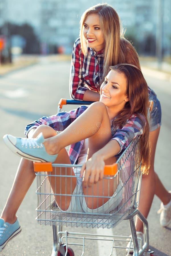 Twee gelukkige mooie tienermeisjes die boodschappenwagentje in openlucht drijven stock fotografie