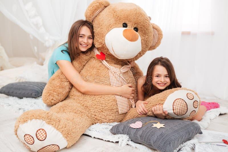 Twee gelukkige mooie zusters die pluche koesteren dragen in speelkamer stock afbeelding