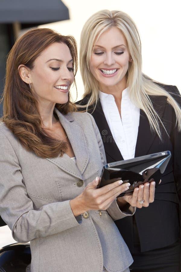 Twee Gelukkige Onderneemsters die een Computer van de Tablet met behulp van royalty-vrije stock foto