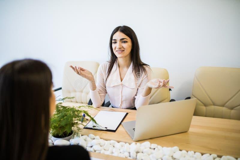 Twee gelukkige onderneemsters die met laptop in een Desktop op modern kantoor coworking stock foto