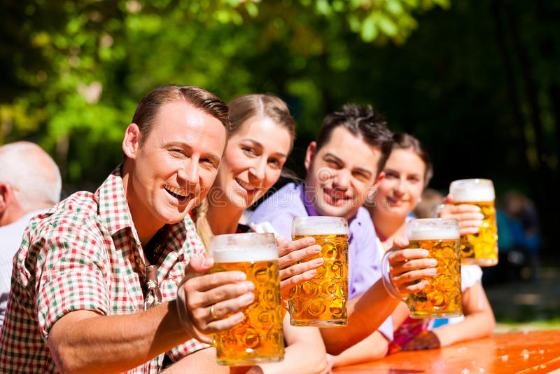 Twee gelukkige paren die in de tuin van het Bier zitten stock foto