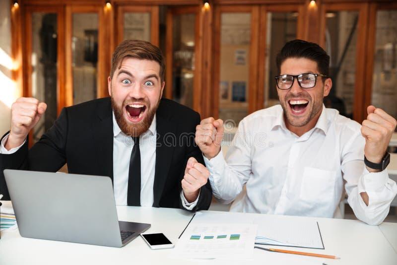 Twee gelukkige partners die met opgeheven handen camera bekijken royalty-vrije stock afbeelding