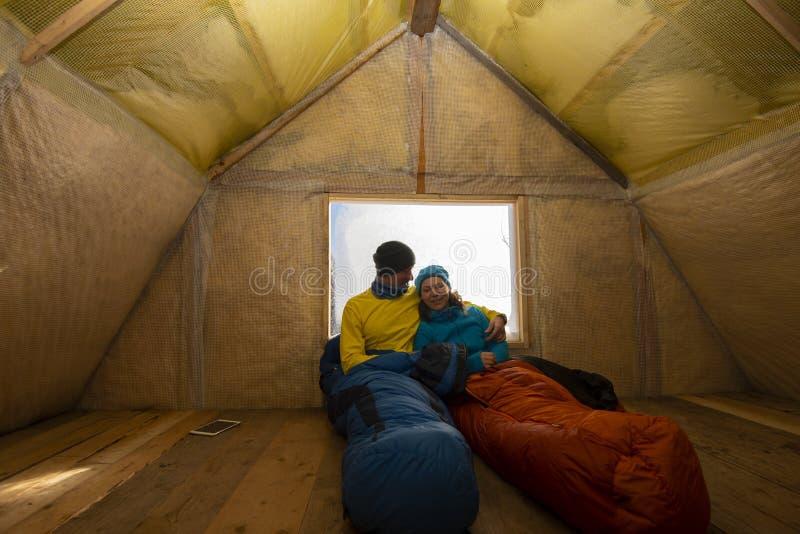 Twee gelukkige reizigers rusten in de oude berghut royalty-vrije stock afbeeldingen