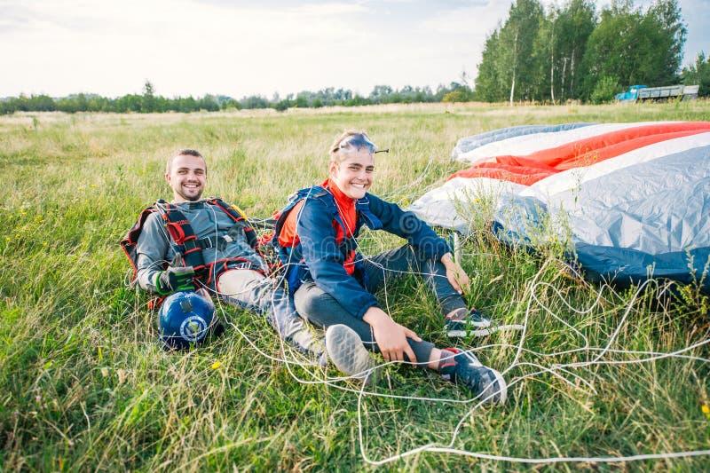 Twee gelukkige skydivers in jumpsuits die op gras zitten Twee die skydivers op het grasgebied is geland stock foto