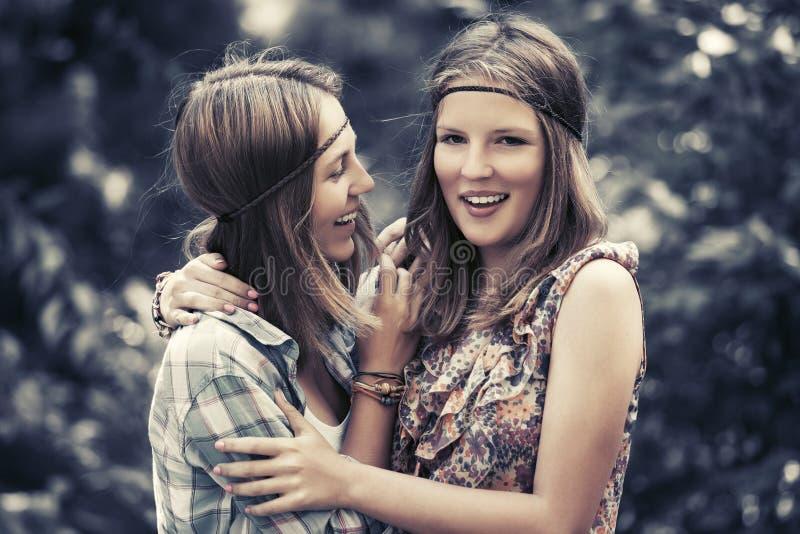 Twee gelukkige tienermeisjes die in de zomerbos lopen royalty-vrije stock foto