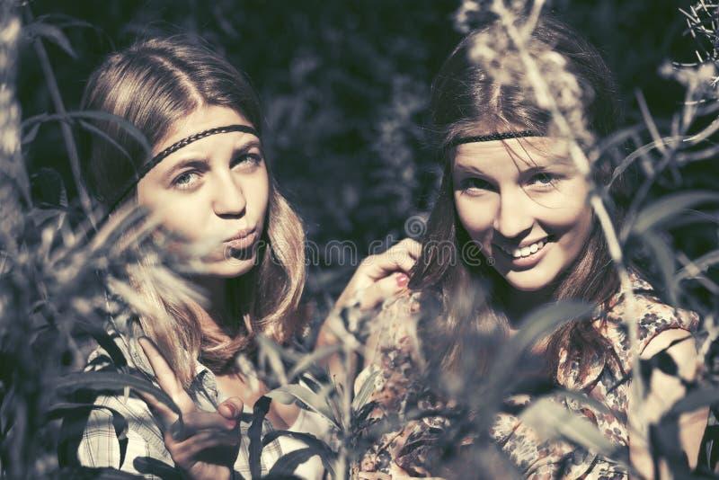 Twee gelukkige tienermeisjes die in de zomerbos lopen royalty-vrije stock fotografie