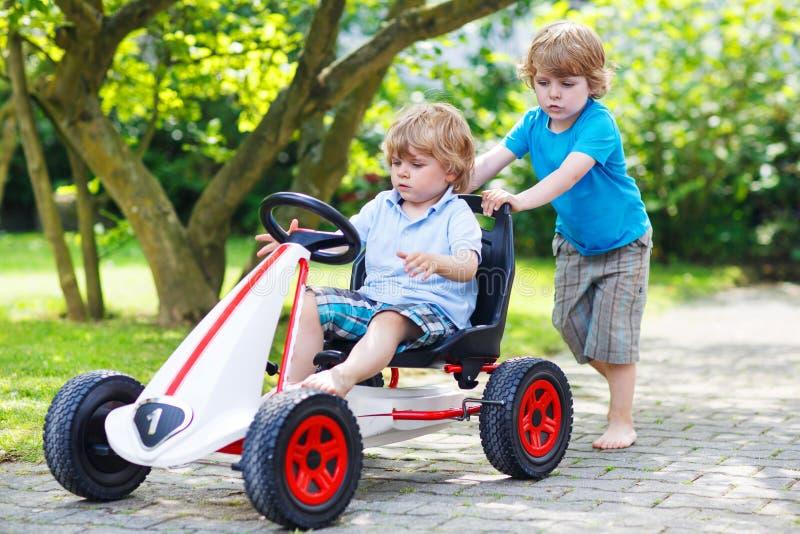 Twee gelukkige tweelingjongens die stuk speelgoed auto drijven royalty-vrije stock foto