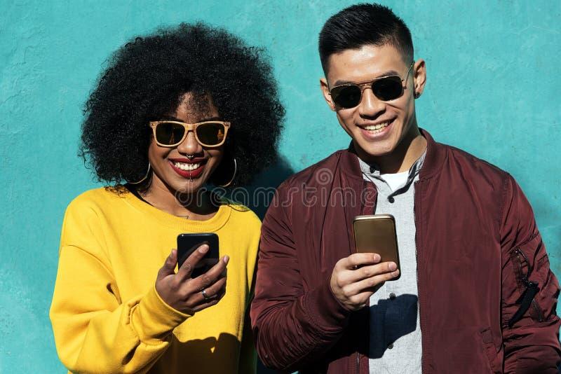 Twee gelukkige vrienden die mobiel in de straat gebruiken Het concept van de vriendschap royalty-vrije stock fotografie
