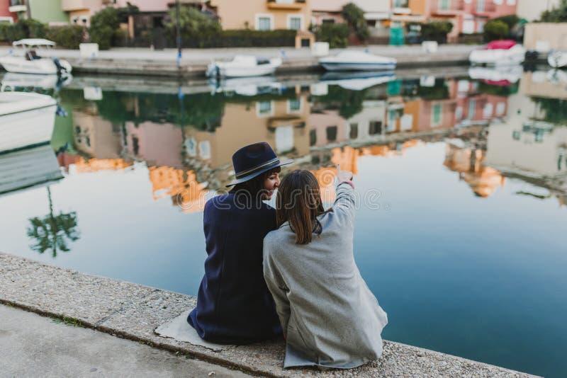 Twee gelukkige vrienden die op het dok bij de haven zitten, pret hebben en op de straat spreken Levensstijl in openlucht stock fotografie