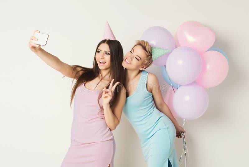 Twee gelukkige vrienden die selfie op smartphone bij partij maken stock foto