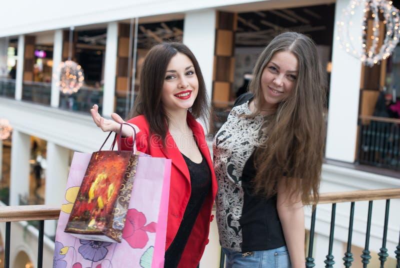 Twee gelukkige vrienden die in wandelgalerij winkelen royalty-vrije stock afbeeldingen