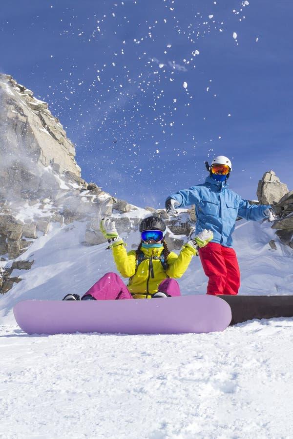 Twee gelukkige vriendensnowboarders hebben pret op skihelling met snowboards in zonnige dag stock foto