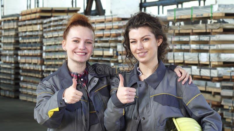 Twee gelukkige vrouwelijke fabrieksarbeiders die tonend duimen bij de opslag omhelzen royalty-vrije stock afbeelding