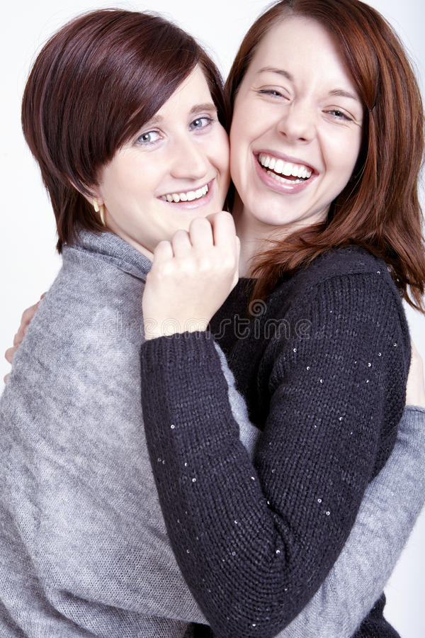Twee gelukkige vrouwelijke vrienden met koffiekoppen royalty-vrije stock afbeeldingen