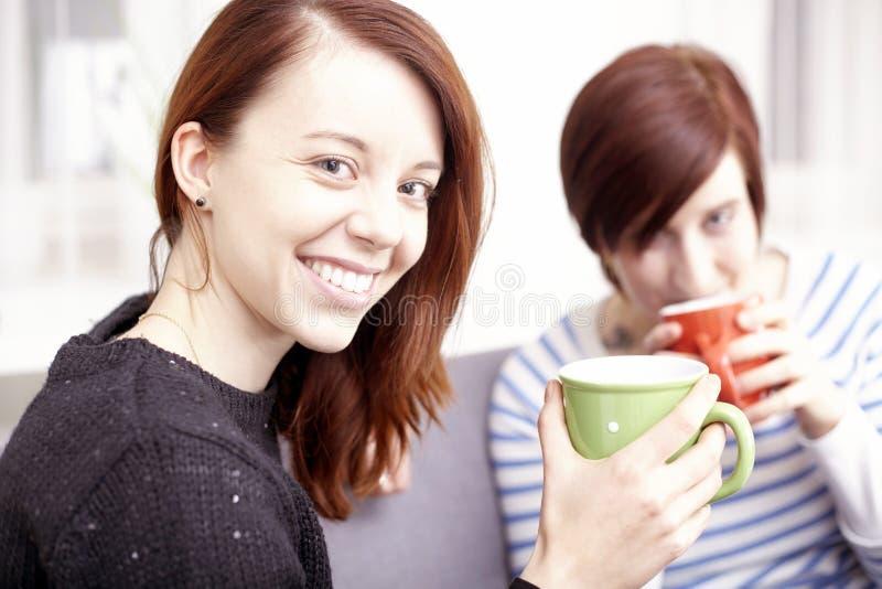 Twee gelukkige vrouwelijke vrienden met koffiekoppen royalty-vrije stock fotografie