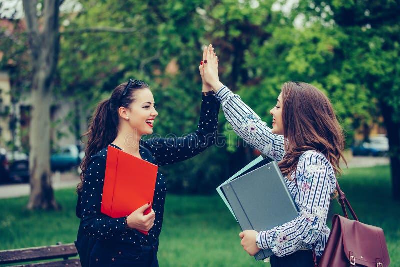 Twee gelukkige vrouwelijke vrienden, studenten geven hoogte vijf na met succes het leren stock afbeeldingen