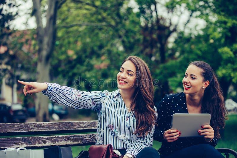 Twee gelukkige vrouwen die digitale tablet houden die plaats richt die zich in een park bevindt stock foto