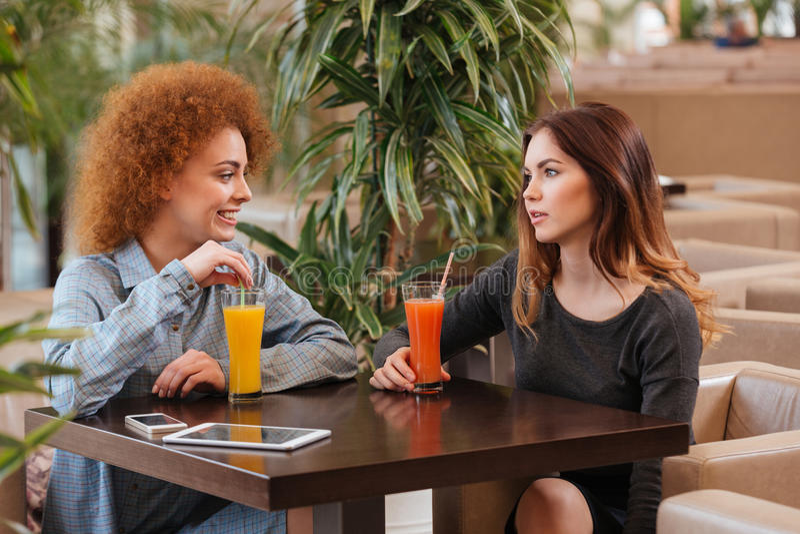 Twee gelukkige vrouwen die en sap in koffie spreken drinken stock foto
