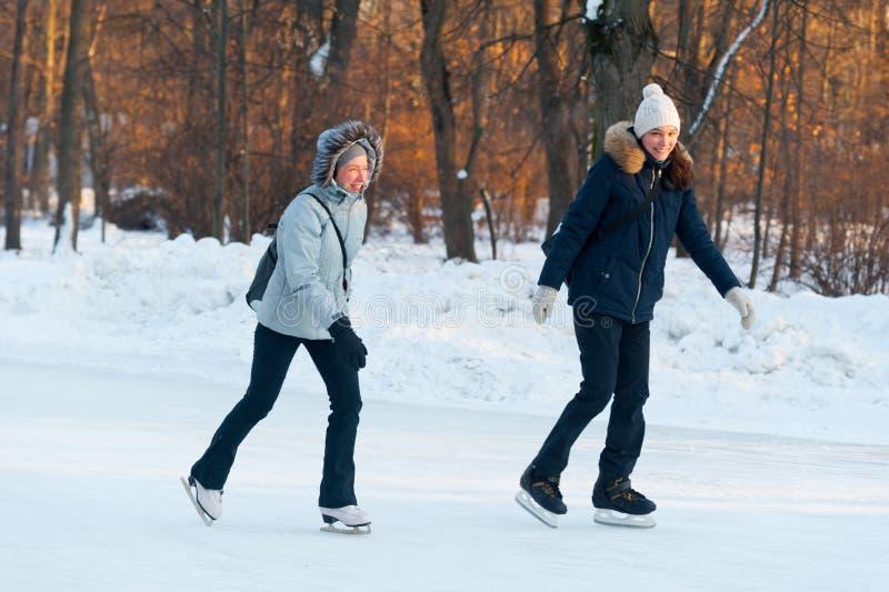 Twee gelukkige vrouwen die en in Sokolniki-Park 23 glimlachen schaatsen 01 2019 royalty-vrije stock foto's