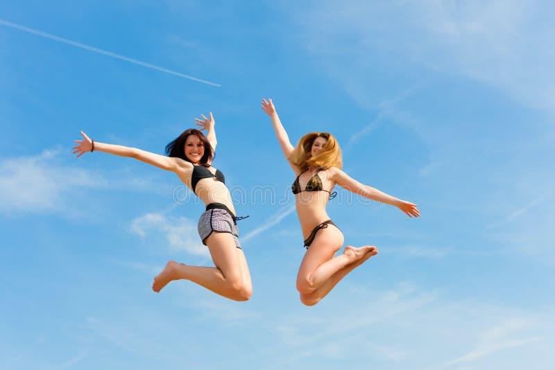 Twee gelukkige vrouwen die hoog met pret springen royalty-vrije stock afbeeldingen