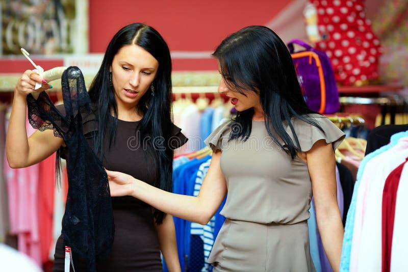 Twee gelukkige vrouwen die in klerenopslag winkelen royalty-vrije stock fotografie
