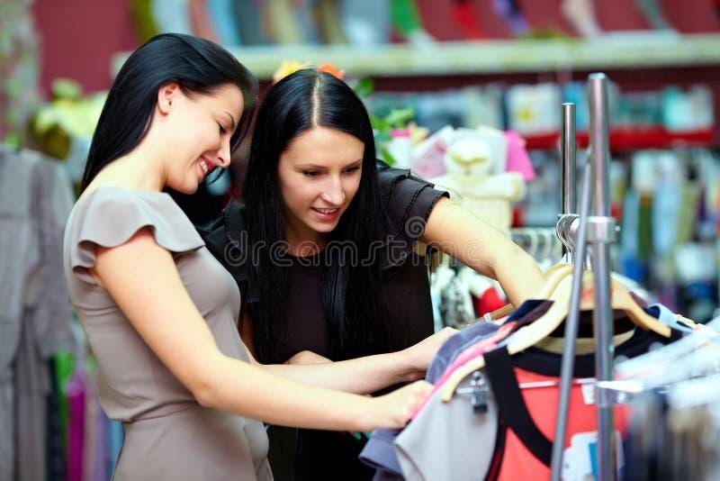 Twee gelukkige vrouwen die in klerenopslag winkelen royalty-vrije stock afbeeldingen