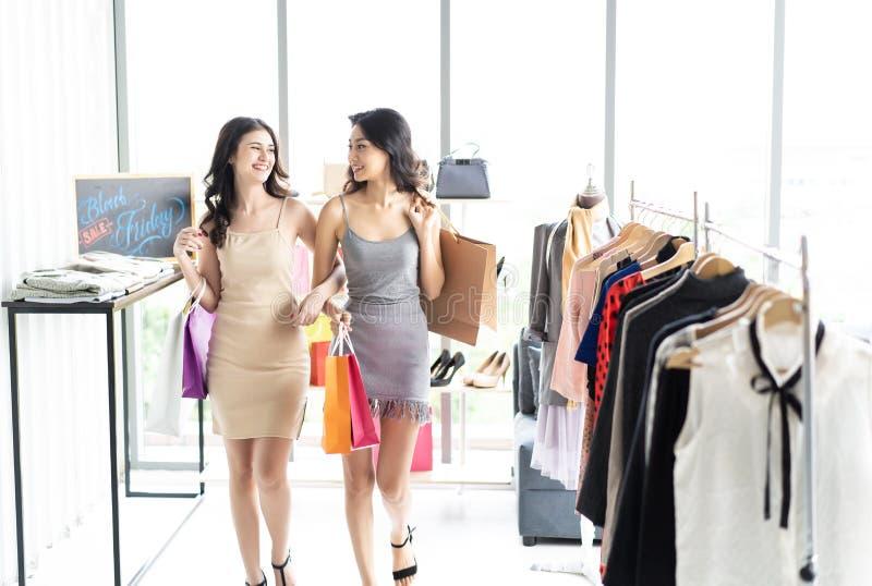 Twee gelukkige vrouwen die met het winkelen zakken in het winkelen in retai genieten van royalty-vrije stock afbeelding