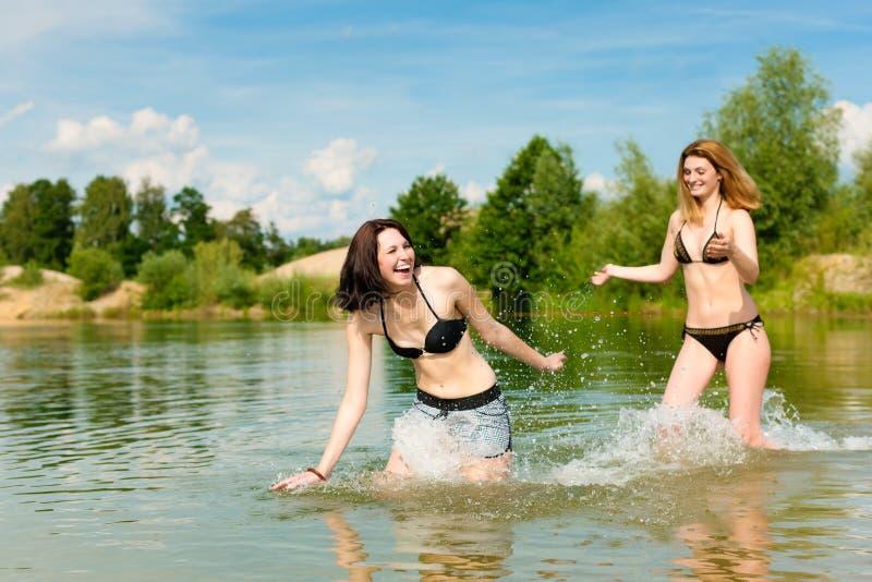 Twee gelukkige vrouwen die pret hebben bij meer in de zomer royalty-vrije stock afbeelding
