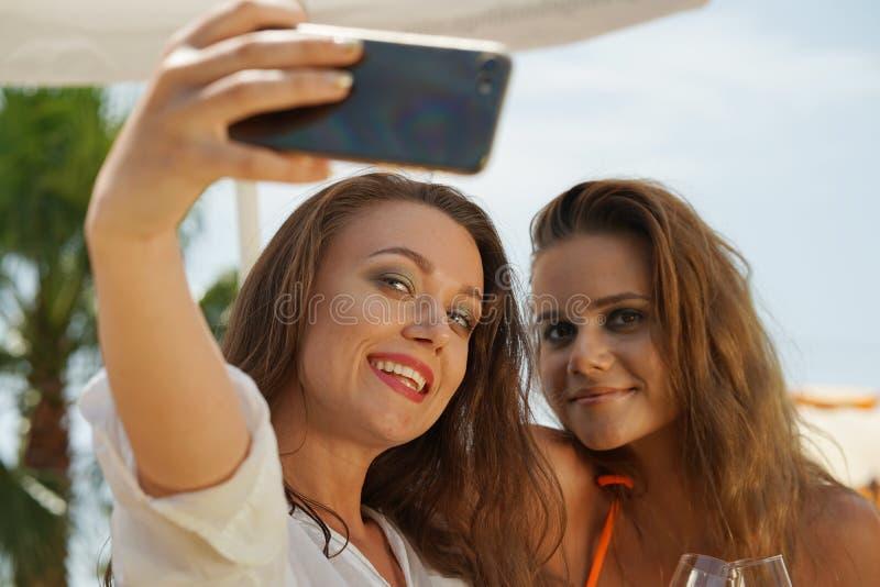 Twee gelukkige vrouwen die selfie nemen stock fotografie