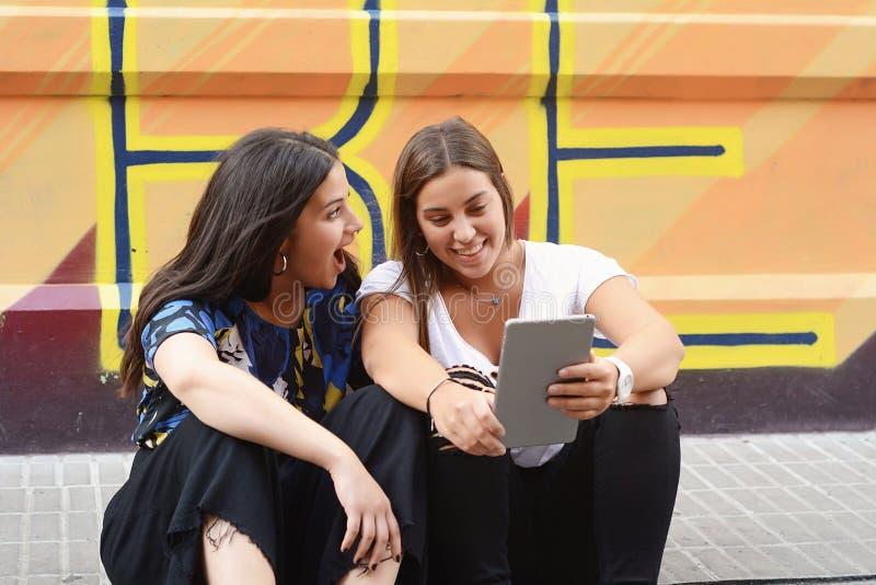Twee gelukkige vrouwen die tabletpc in de straat onderzoeken royalty-vrije stock afbeeldingen
