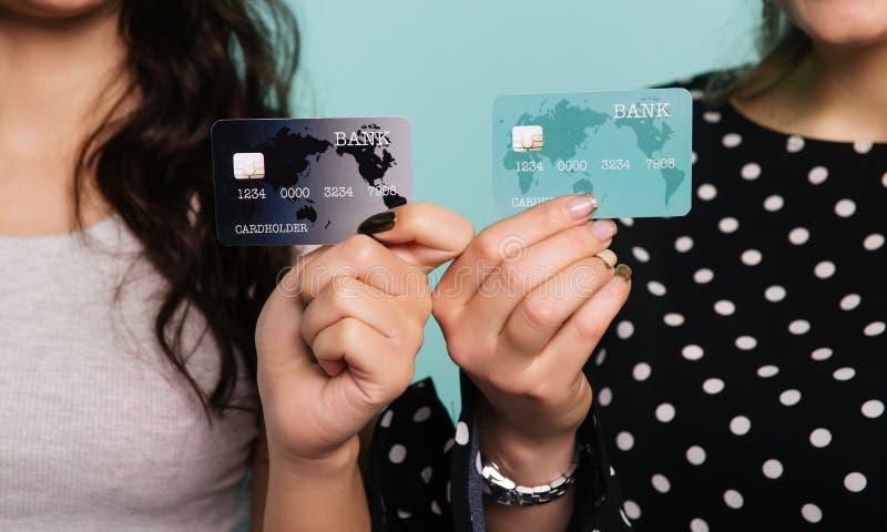 Twee gelukkige vrouwen in kleding die samen terwijl het tonen van creditcards bij camera op blauwe achtergrond stellen royalty-vrije stock fotografie