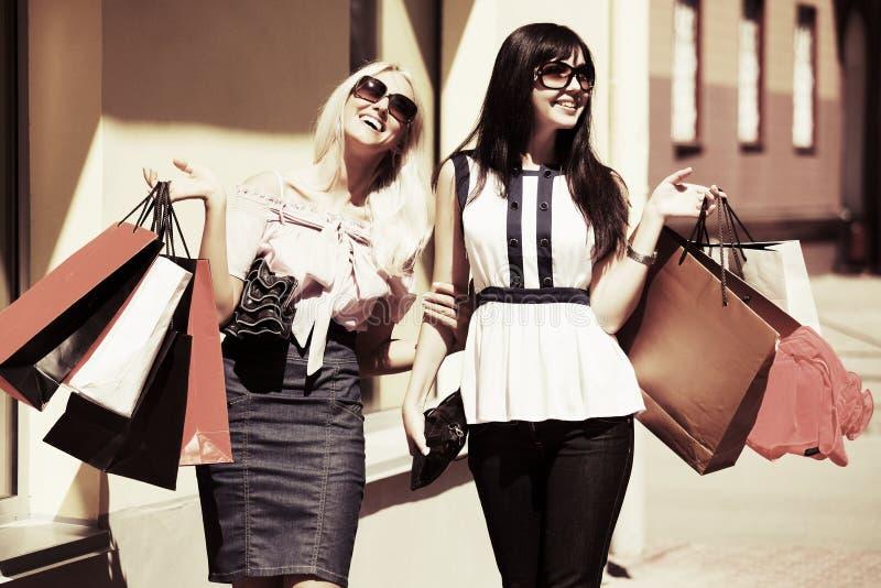 Twee gelukkige vrouwen met het winkelen zakken stock afbeelding