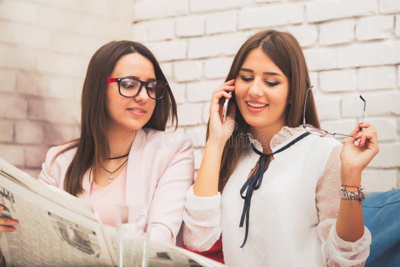 Twee gelukkige vrouwen zoeken een baan in de krant royalty-vrije stock foto