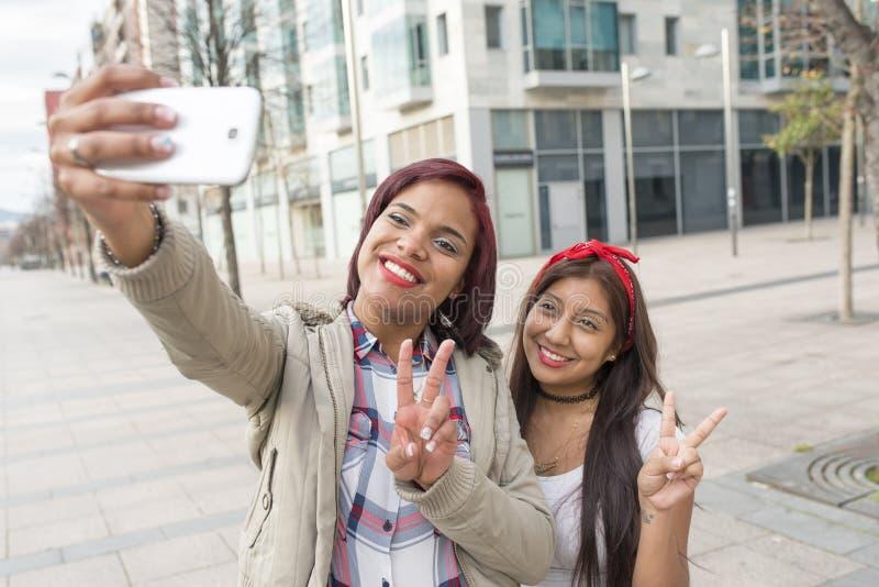 Twee gelukkige vrouwenmeisjes die een selfie in de straat nemen stock afbeeldingen