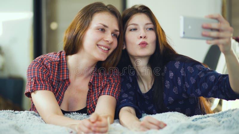 Twee gelukkige vrouwenvrienden die in bed liggen en selfie in ochtend maken en hebben pret op bed stock fotografie