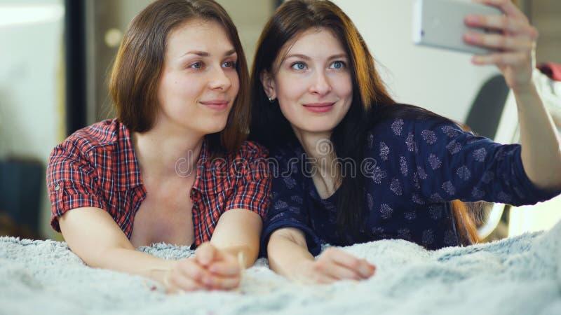 Twee gelukkige vrouwenvrienden die in bed liggen en selfie in ochtend maken en hebben pret op bed royalty-vrije stock afbeeldingen