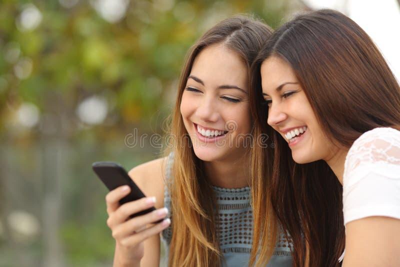 Twee gelukkige vrouwenvrienden die een slimme telefoon delen stock afbeeldingen