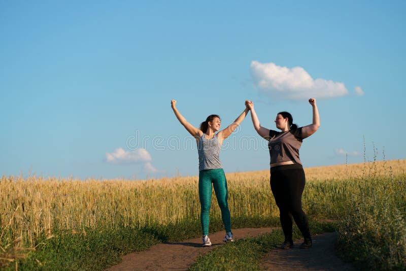 Twee gelukkige vrouwenvrienden geven vijf na jogging royalty-vrije stock afbeelding