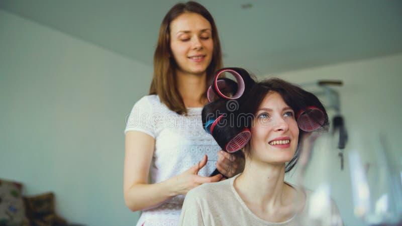 Twee gelukkige vrouwenvrienden maken het kapsel van de pretkrulspeld elkaar en hebben thuis pret stock foto