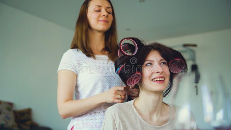 Twee gelukkige vrouwenvrienden maken het kapsel van de pretkrulspeld elkaar en hebben thuis pret stock afbeeldingen