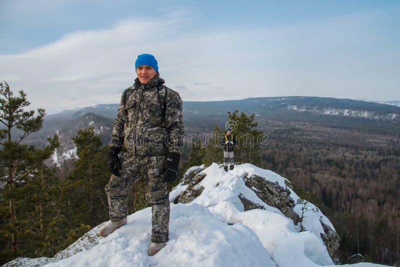 Twee gelukkige wandelaars bij bergbovenkant in de winterdag stock afbeelding