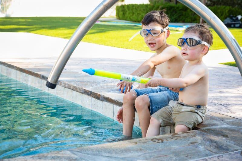 Twee Gemengde Ras Chinese Kaukasische Broers door de Pool in Zwemmende Beschermende brillen stock afbeelding
