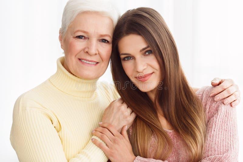 Twee generaties Het rijpe Moeder en Dochter Koesteren stock afbeelding