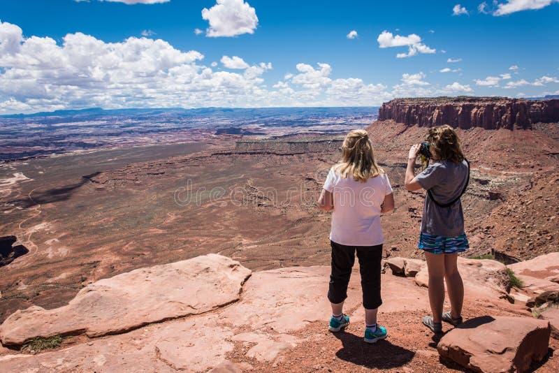 Twee genieten de volwassen de vrouwenmoeder en dochter van de toneelmening van het Nationale Park van Canyonlands in Utah stock afbeeldingen
