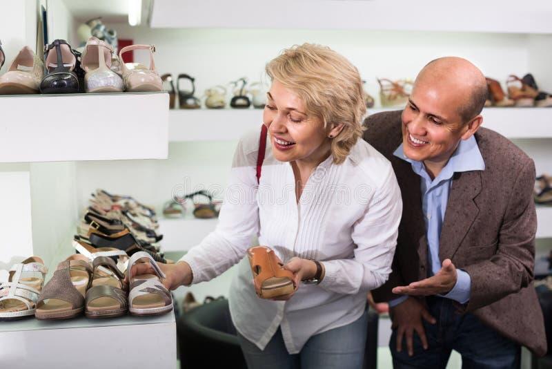 Twee gepensioneerden die samen paar schoenen in manieropslag kiezen stock afbeeldingen