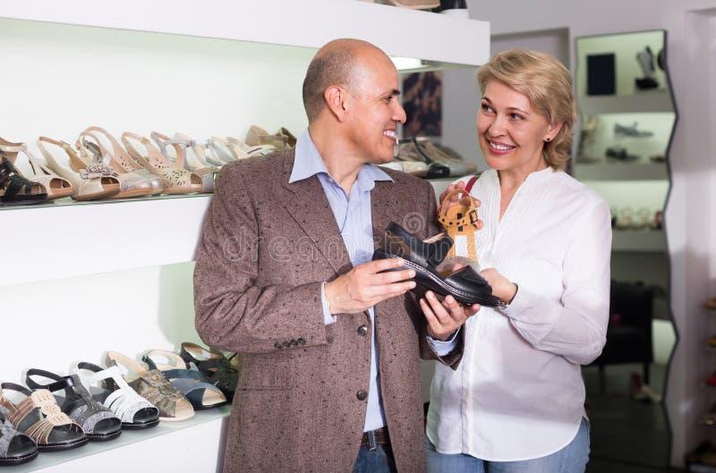 Twee gepensioneerden die samen paar schoenen in manieropslag kiezen stock fotografie
