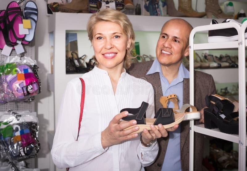 Twee gepensioneerden die samen paar schoenen in manieropslag kiezen stock foto