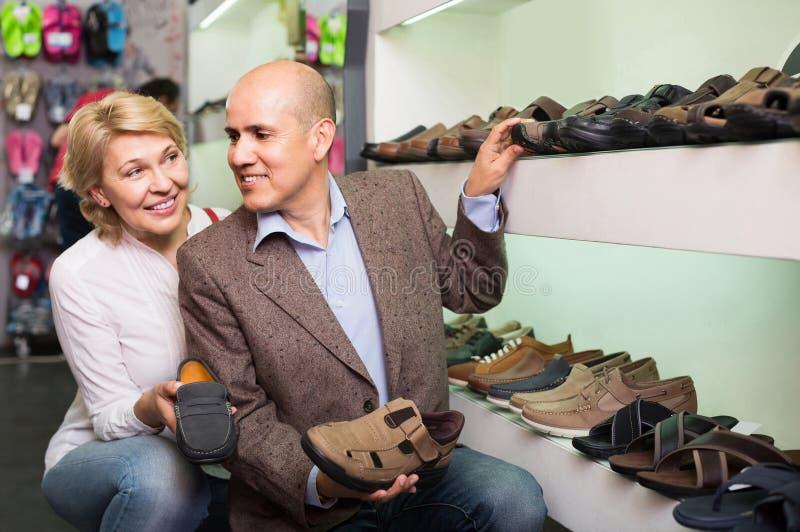 Twee gepensioneerden die samen paar schoenen voor mensen in schoensto kiezen royalty-vrije stock afbeelding